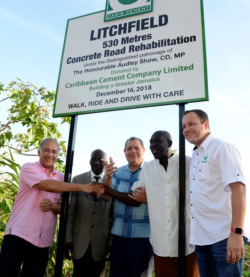Parris Lyew-Ayee, Chairman of Carib Cement; Councilor Leroy Mitchell of the Walderston Division of the Manchester Municipal Council; Collin Walters, member of the community; The Hon Audley Shaw, MP and Peter Donkersloot, General Manager of Carib Cement following the unveiling of the sign yesterday marking the opening of the 530metres of concrete road donated by Carib Cement to Litchfield, Manchester.