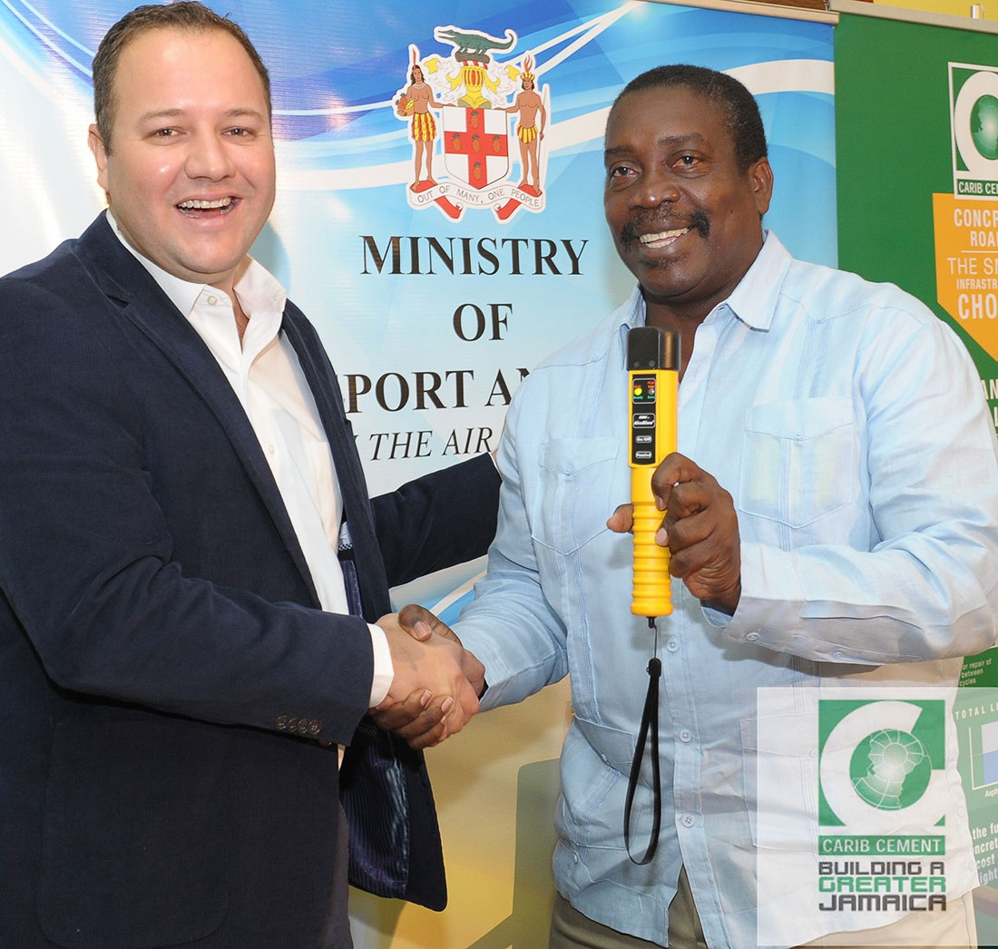 Peter Donkersloot, Carib Cement's General Manager presents a breathalyzer to the Hon. Robert Montague, Minister of Transport and Mining